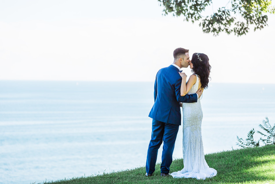 Bride and groom kiss in front of Lake Ontario waterfront at Toronto Hunt Club