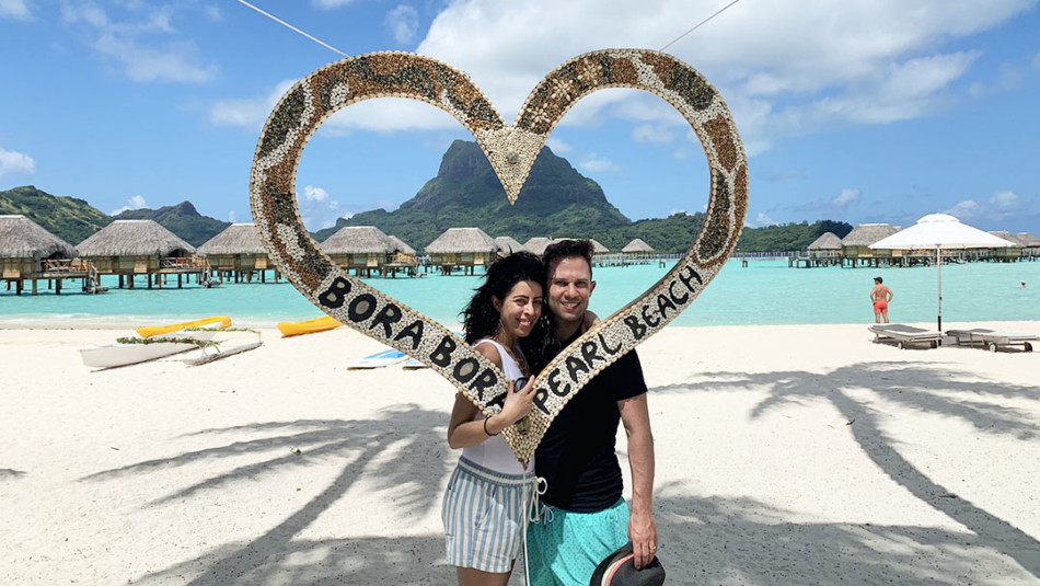 Honeymooners in front of Heart shaped sign on the beach at Pearl Resort in Bora Bora